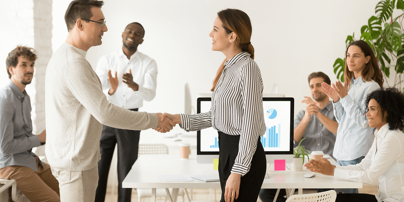 man and woman shaking hands in an office environment surrounded by team members
