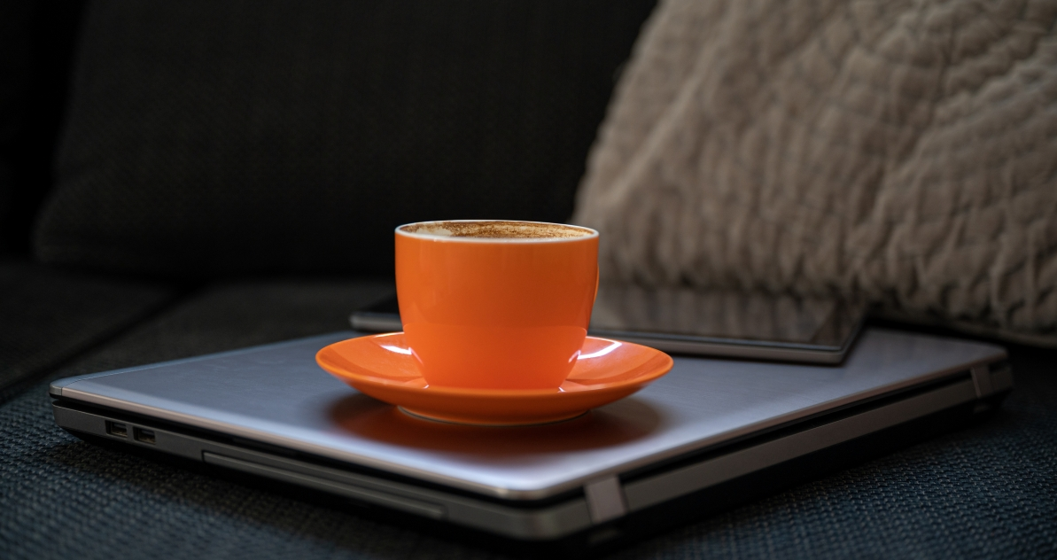 Orange coffee cup on laptop sitting on couch